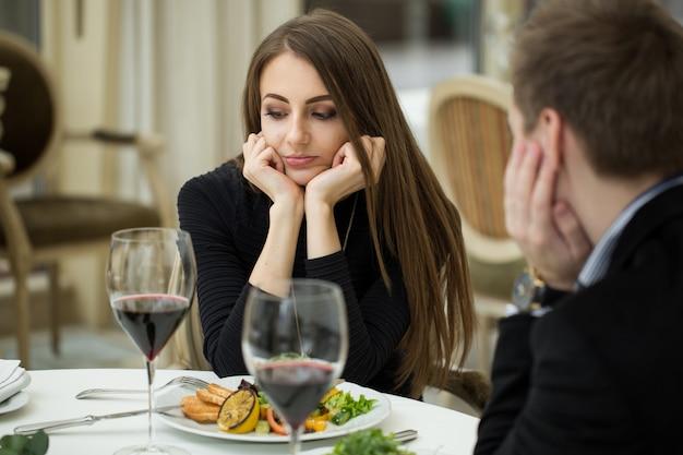 レストランで悪い日に怒りに満ちた表情のジェスチャーを作る若い女性