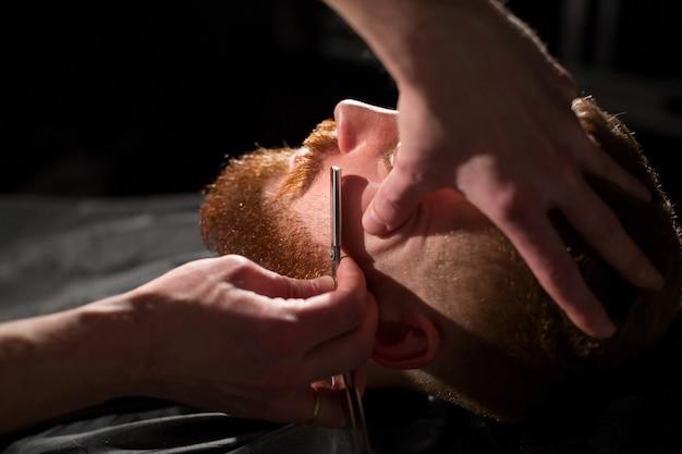 Парикмахер бреет мужскую бороду ножом. красивый бородатый мужчина бреется у парикмахера в парикмахерской