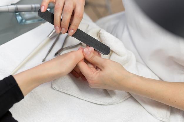 ビューティーサロンで爪やすりで爪をファイリング女性の手