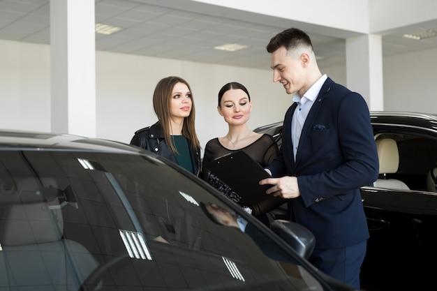 車のディーラーと女の子の友人のカップルが車のディーラーで車を選ぶ