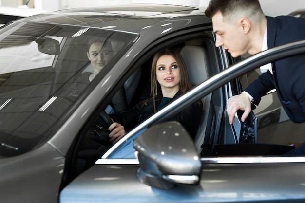 若い女の子がサロンで車を選ぶ