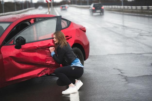 事故後に壊れた車の近くに座っている女性。助けを呼びます。自動車保険