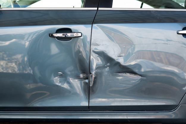 青い車への板金の損傷。交通事故