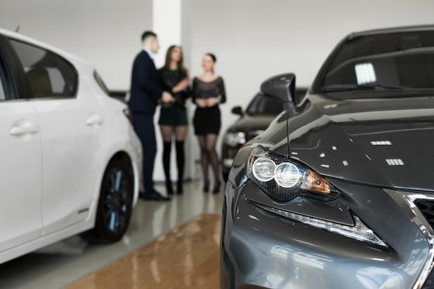 自動車事業、自動車販売-自動車販売店にいる女の子の友人のカップルが自動車販売店で自動車を選ぶ