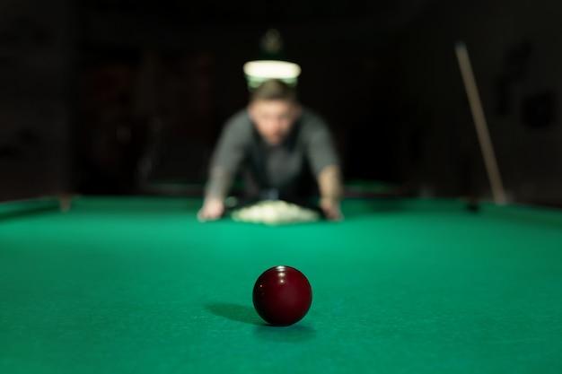 ビリヤードのゲーム。男は緑のビリヤードテーブルにボールを置きます。