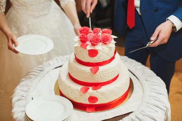 Свадебный пирог. жених и невеста разрезали торт на банкете.
