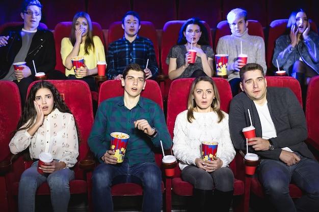 Молодые напуганные пары смотрят в кинотеатрегруппа людей смотрит фильм ужасов в кинотеатре фильм ужасов