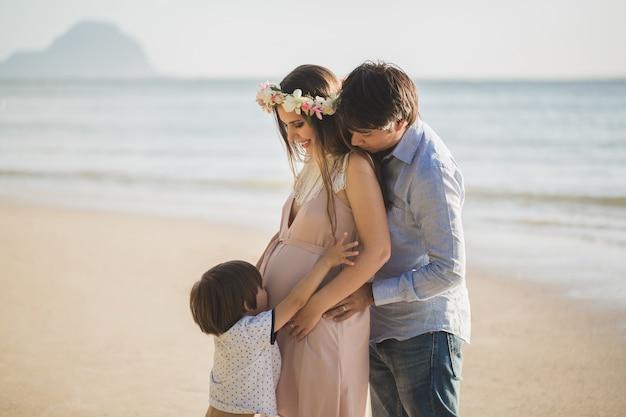 Беременная женщина, малыш и смешанная раса мужчина на пляже