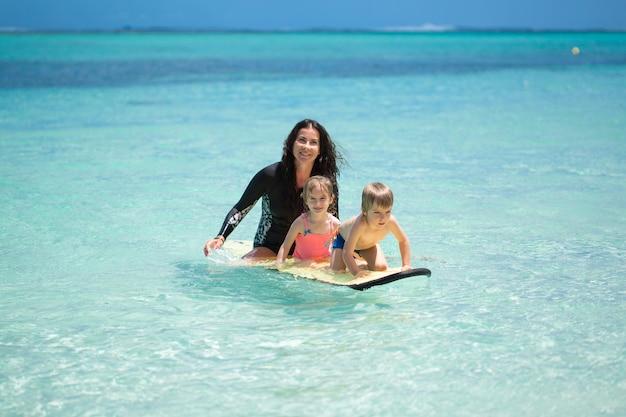 双子、男の子と女の子のお母さんが黒板に海でサーフィン