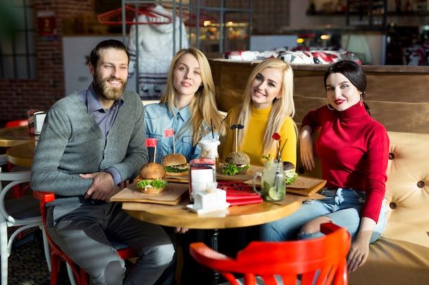 人々はカフェのテーブルで一緒に夕食をとります。幸せな友達がレストランでハンバーガーを食べ、カクテルを飲む