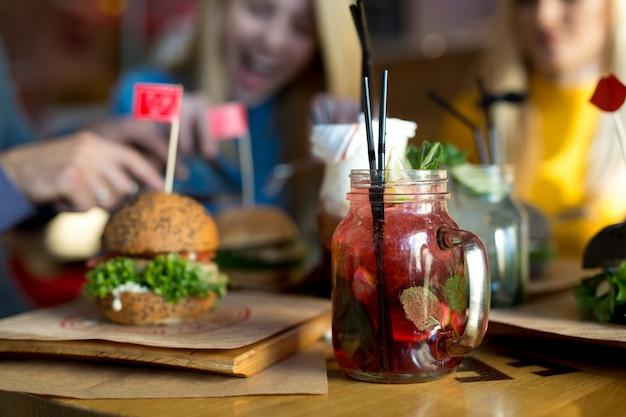 レストランの木製テーブルでハンバーガーとカクテル