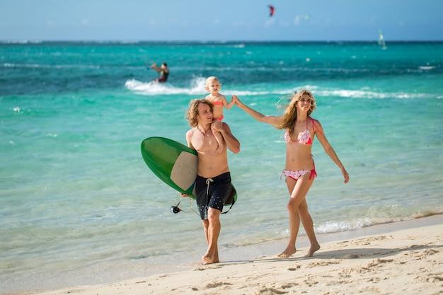 スポーツ家族のお父さん、お母さんと娘のビーチの上を歩く