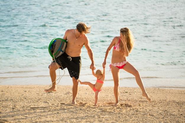 ビーチで彼の娘と遊ぶ若くて美しい親