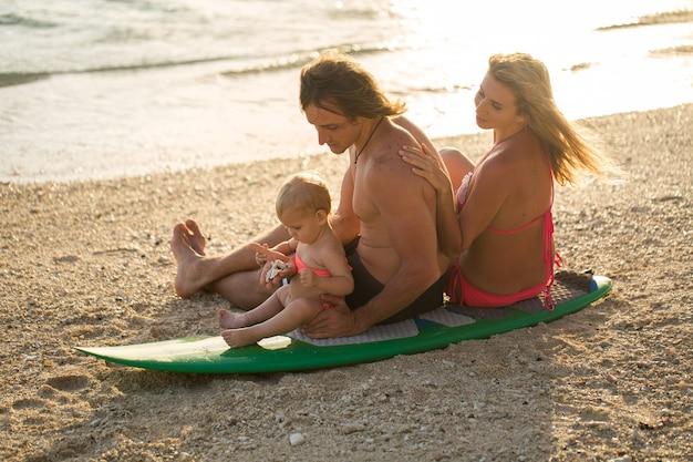 サーフィン。幸せな家族がサーフボードに座っています。家族、スポーツ、楽しみについての概念