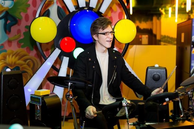 Молодой человек играет на электронных барабанах
