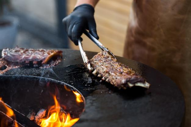 Свиные ребрышки на гриле с соусом барбекю на гриле. фестиваль уличной еды