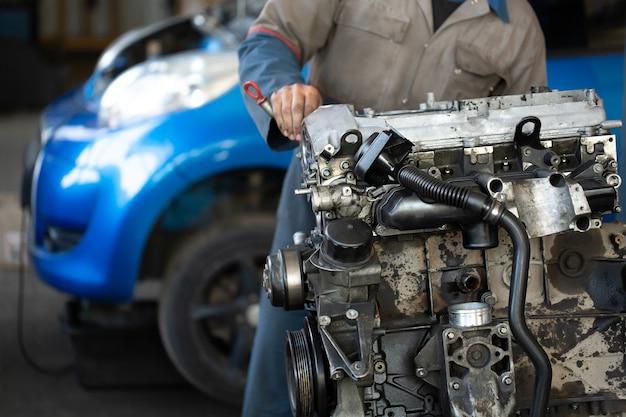 Мастер, автомеханик ремонтирует двигатель автомобиля на сто
