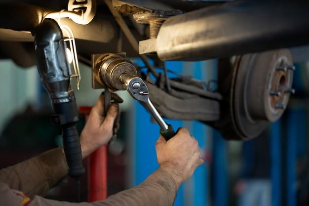 Автомеханик ремонтирует подвеску поднятого автомобиля на станции автосервиса