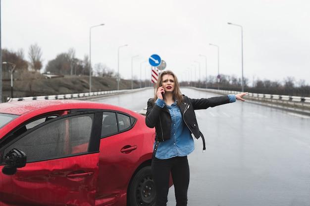 赤い車のそばに立っているサービスを呼び出す女性