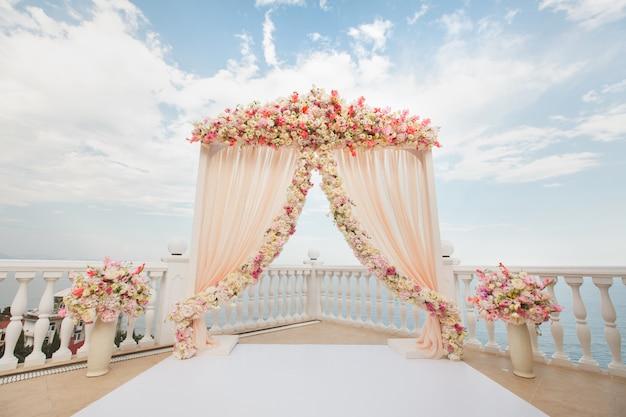Свадебная арка персикового цвета с цветами на море. вазы со свежими цветами.