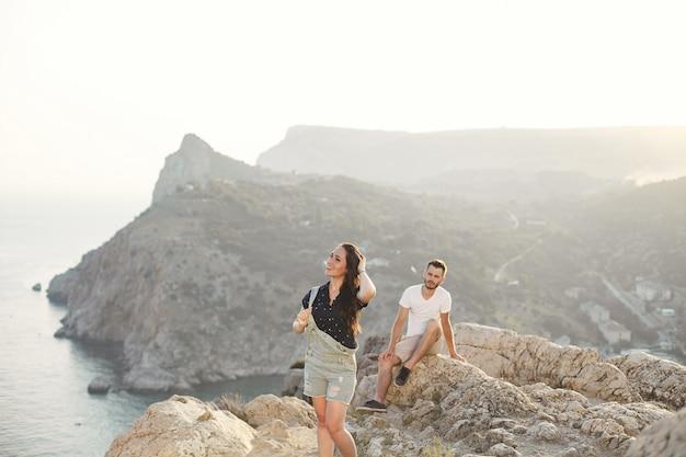 Влюбленные, парень и девушка, на краю обрыва на фоне гор и океана.