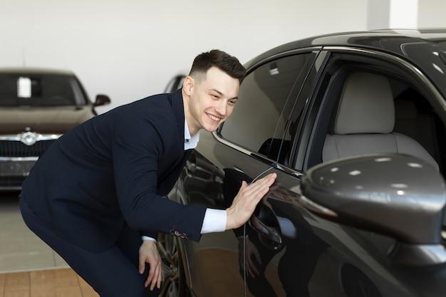 古典的な紺のスーツでハンサムな青年実業家がモーターショーで車を調べながら笑っています。