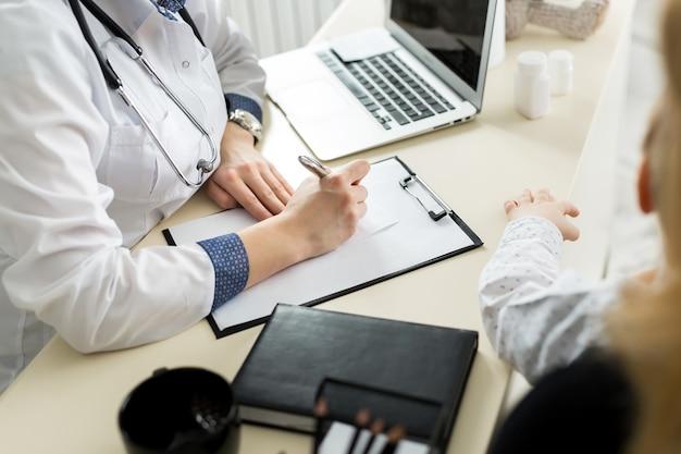 Крупный план женского доктора, заполняющего медицинскую форму