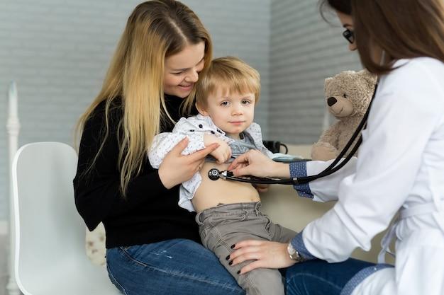 Профессиональный врач общей педиатр в белом халате слушает звук легких и сердца ребенка пациента с помощью стетоскопа. врач осматривает ребенка женского пола после консультации в больнице