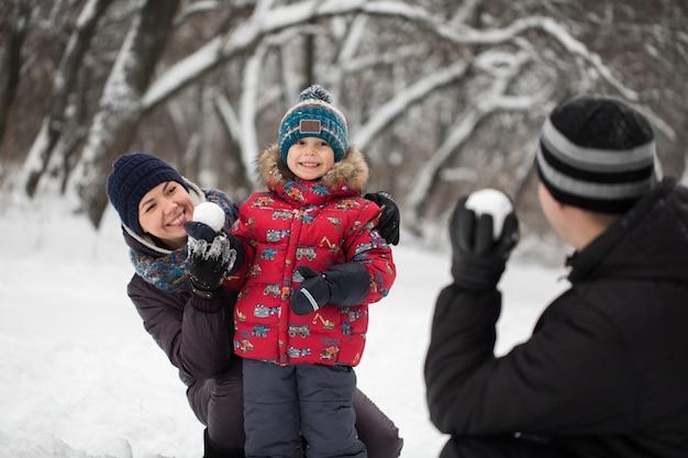 Отец, мать и сын играют в снежки в зимнем парке