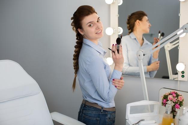 鏡の近くに手でブラシを持つ少女アーティスト