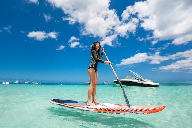 美しい女性は美しい晴れた日にサーフィンをしています