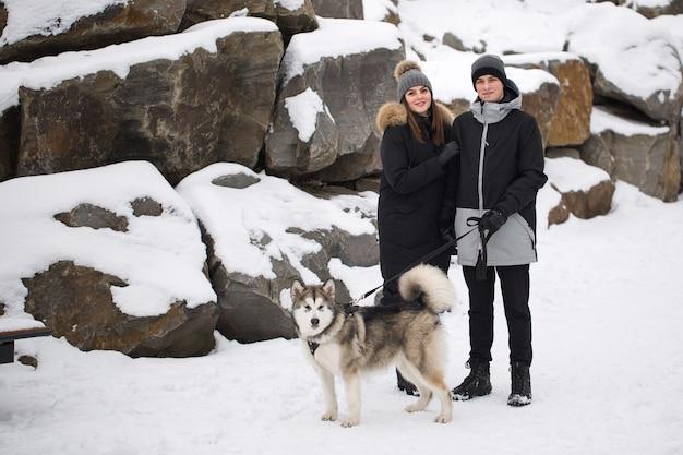 Красивая семья, мужчина и девушка в зимнем лесу с собакой. поиграйте с собакой сибирской хаски.