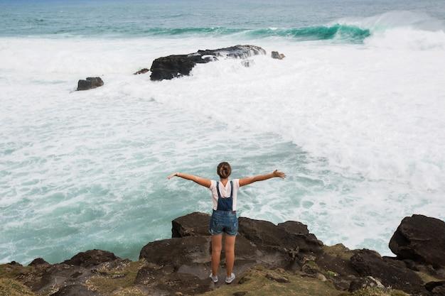 山の頂上に腕を上げて立っている自由旅行者の女性と美しい海の景色をお楽しみください。モーリシャス