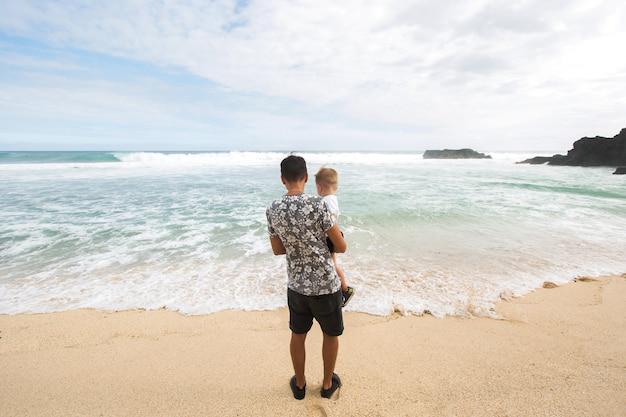 Отец и сын, держась за руки, вместе гуляя по пляжу
