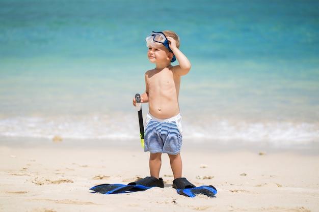 Маленький мальчик с маской для подводного плавания и ластами плавать на пляже