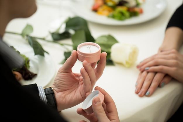 レストラン、クローズアップでガールフレンドに結婚のプロポーズをする男性