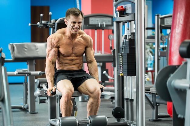 運動の強力なボディービルダーは、不均一なバーのスポーツジムホールで運動を実行します