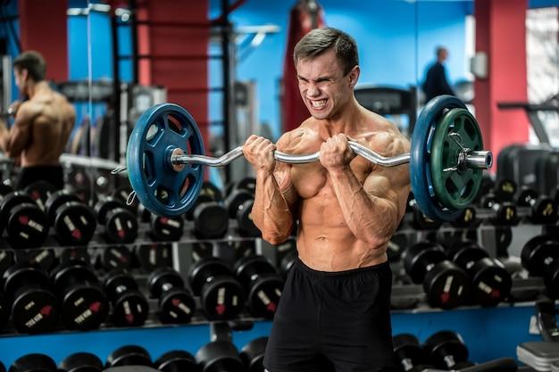 ジムでエクササイズを立っている非常に強力な運動選手