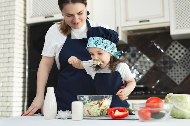 思いやりのある母親が小さな娘にキッチンでサラダを準備する方法を教え、若い母親と魅力的な甘い女の赤ちゃんがサラダをドレスアップし、塩を入れて、味わいます。
