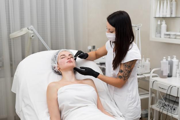 美容師は、患者の顔に白い鉛筆の輪郭を描きます。輪郭を描く前の回路図マーキング。美容整形手術のための顔のクローズアップ準備