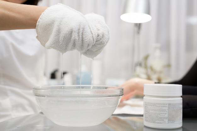 美容師は、美容院で若い女の子のケアの手のためのスパトリートメントを行います。ネイリストは、スクラブとマッサージの後、クライアントにぬれたタオルで手を拭きます