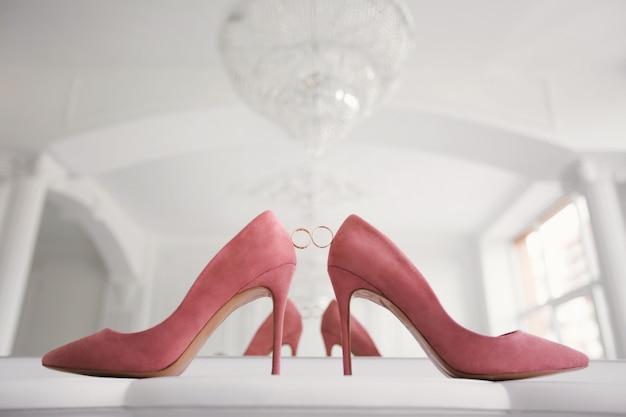 Золотые обручальные кольца между свадебными туфлями невесты