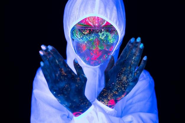 Доктор в ультрафиолетовом неоновом свете в защитном костюме и маске для лица показывает знак жеста стоп