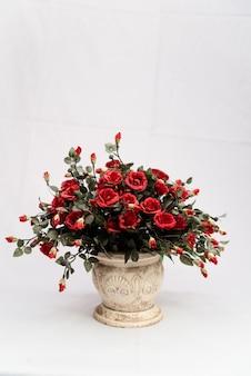 Красивые красные розы в керамическом горшке