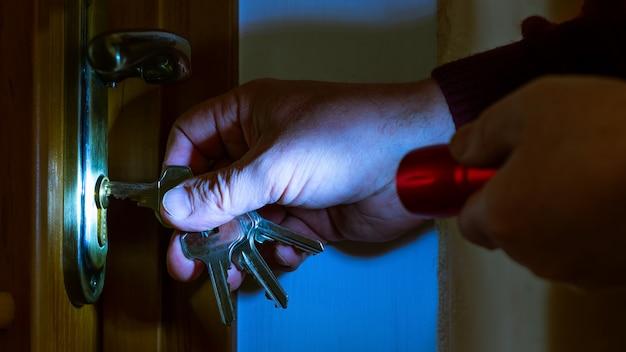 泥棒が夜に懐中電灯でドアを開けます。アパートの強盗、住居への違法侵入