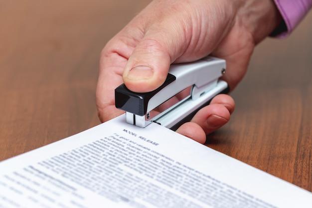 オフィスホッチキスのビジネスマンはドキュメント、紙シートを固定します_