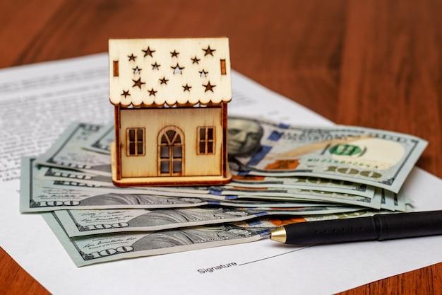 家の売買に関する文書に署名するためのハンドル。お金の近くの家のモデルと住宅購入の文書