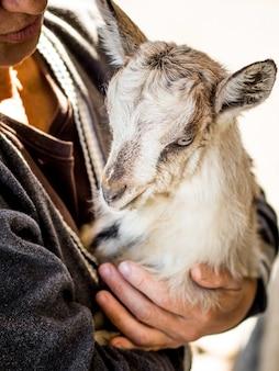Маленькая коза в руках женщины. женщина беспокоится о мелких животных