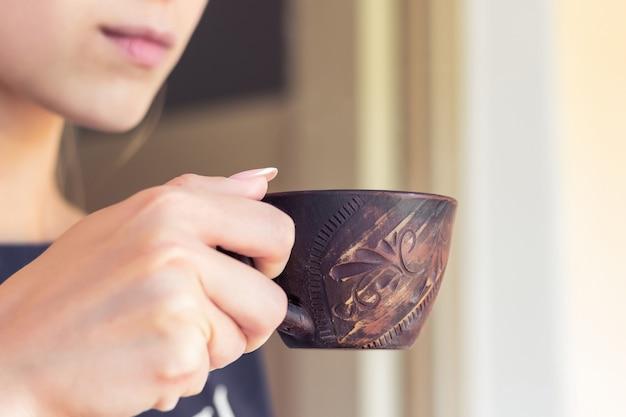 女の子は仕事の合間にコーヒーを飲む