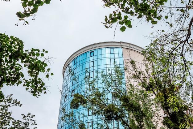塔の形をした丸い形のモダンな建物。ガラスのファサードを持つ近代的なオフィスビル